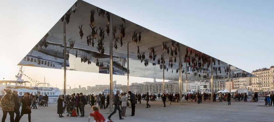 Sur le quai de la Fraternité, une toiture en Inox soutenue par huit poteaux de 6,5 m de hauteur, renvoie une image inversée des promeneurs.