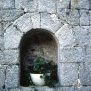 Niche couverte par un arc dont le plein-cintre est réalisé au moyen de cinq claveaux - éléments en pierre taillés en forme de coin.