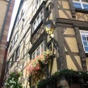 Maison alsacienne en ossature bois dont les étages sont en encorbellement part rapport à la rue - photo: Françoise Miller.