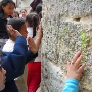 Enfant éprouvant la texture d'un des piliers de la cathédrale Saint Pierre de Montpellier (34) photo: Odile Besème.